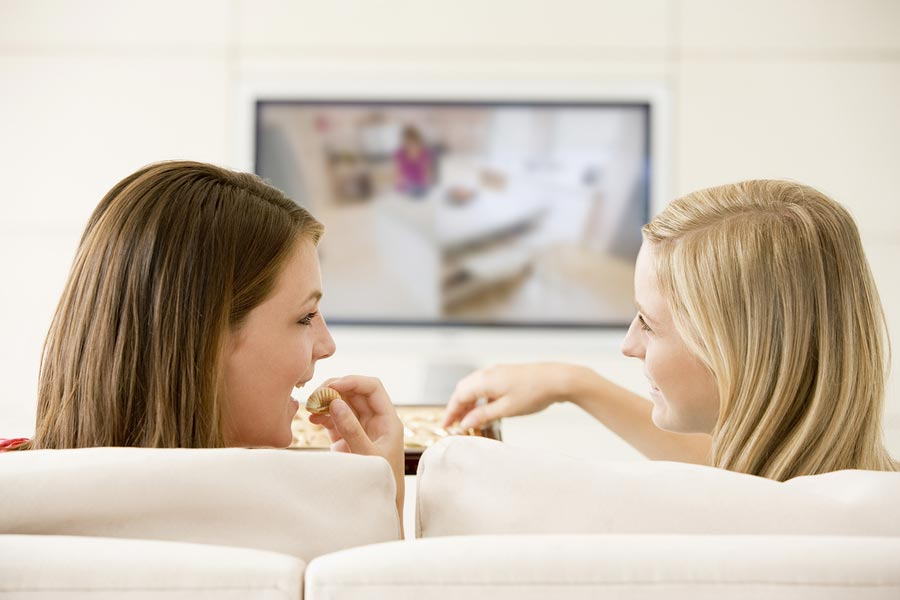 Teen girls relaxing at home on sofa watching tv