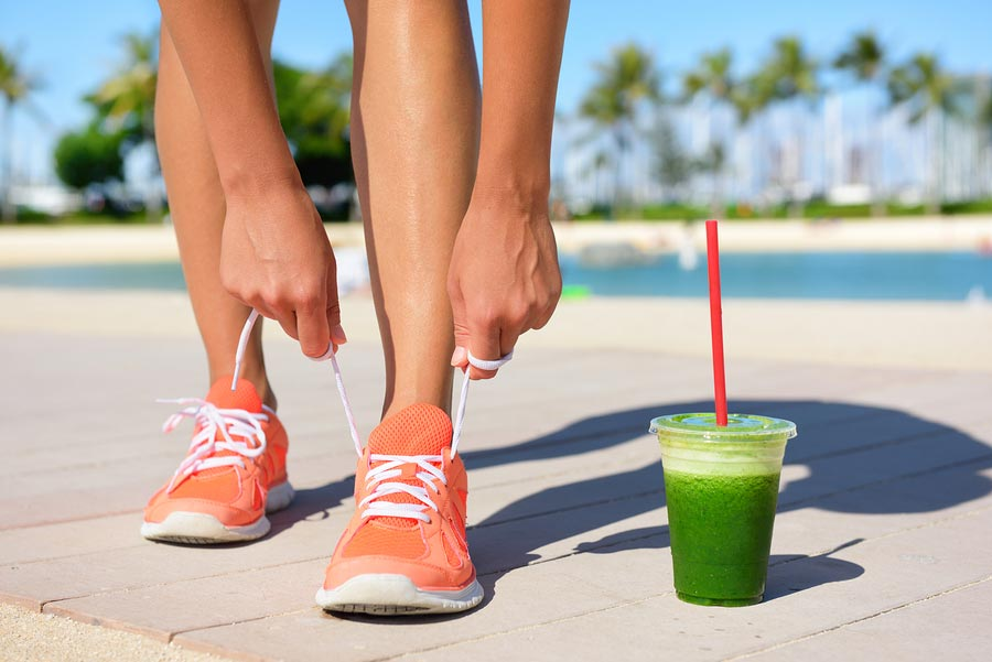 Running woman runner with green vegetable smoothie. Fitness and